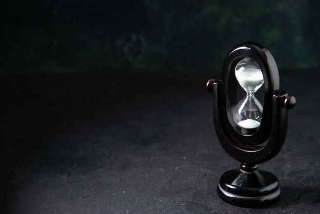 Vista frontale della clessidra nera su superficie scura