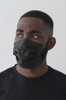 Вид спереди черный человек в маске и смотрит в сторону