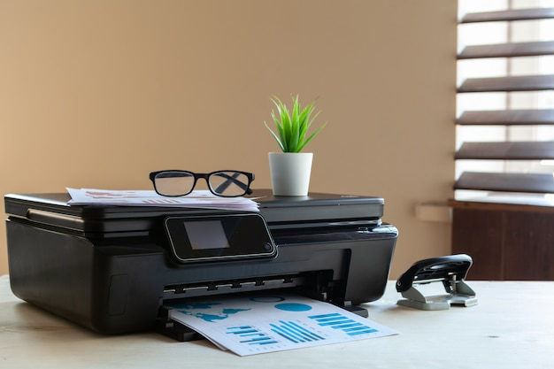 Front view of a black printer machine on a table