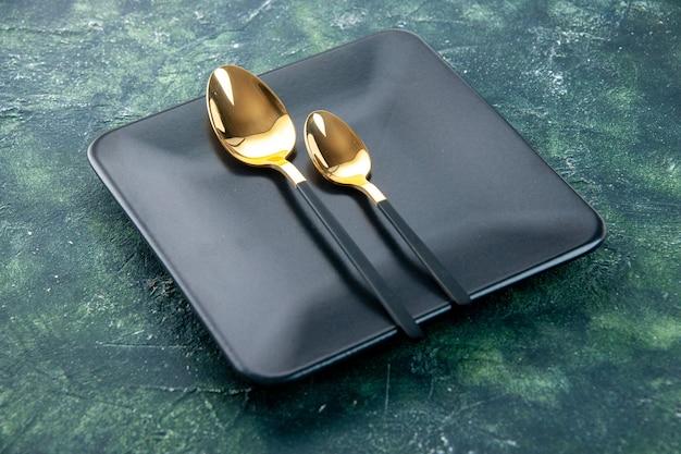 어두운 배경에 황금 숟가락으로 전면보기 검은 사각형 접시