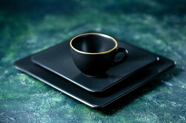 Вид спереди черные квадратные тарелки с черной чашкой на темно-синем фоне