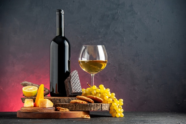 Front view black wine bottle red wine in glass cheese cut lemon a piece of dark chocolate biscuits grapes on wooden boards on dark red table with copy place
