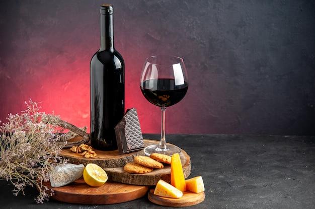 Вид спереди бутылка черного вина красное вино в стекле сыр нарезанные кусочки лимона темного шоколада на деревянных досках ветка сушеных цветов на красном столе место для копирования