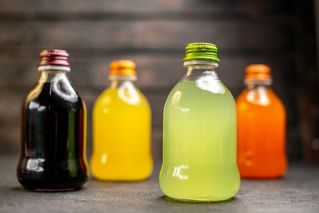 Front view black yellow green and orange juice in bottles