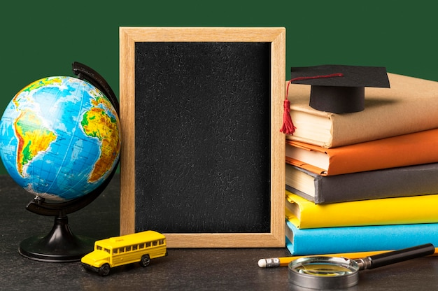 Front view of blackboard with academic cap and globe