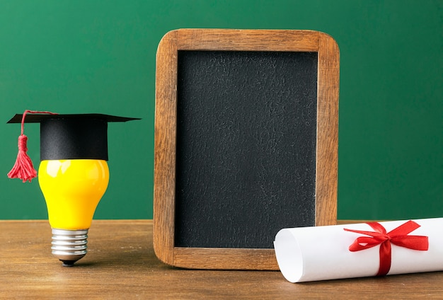 Front view of blackboard with lightbulb and academic cap