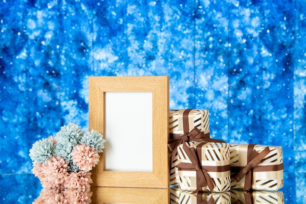 Front view blank picture frame holiday presents flowers on blue abstract background