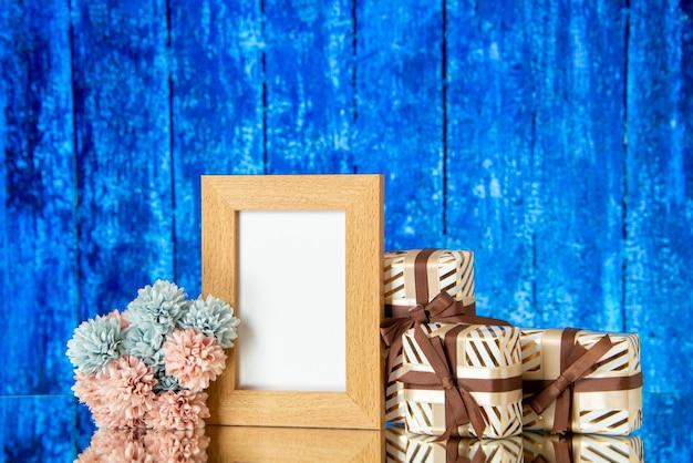 La vista frontale della vacanza della cornice in bianco presenta i fiori su fondo di legno blu
