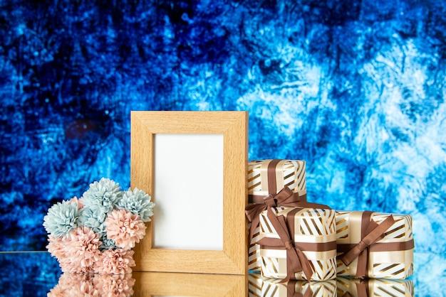 Vista frontale cornice vuota il giorno di san valentino presenta fiori isolati su sfondo astratto blu scuro