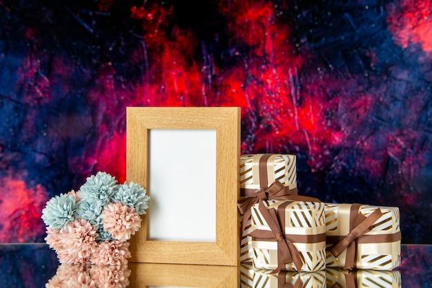 Vista frontale cornice vuota il giorno di san valentino presenta fiori isolati su sfondo astratto rosso scuro