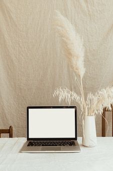 Front view blank screen laptop computer and fluffy pampas grass against pastel beige linen wall
