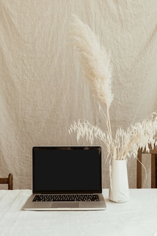 Front view blank screen laptop computer and fluffy pampas grass against pastel beige linen wall.