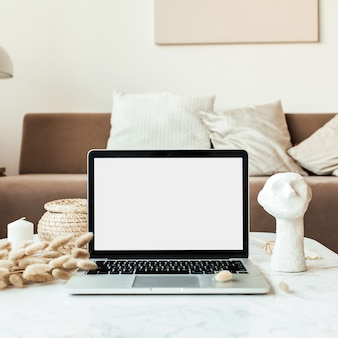 Front view of blank screen laptop on marble table with reeds foliage, bust. modern interior design with comfortable sofa with pillows
