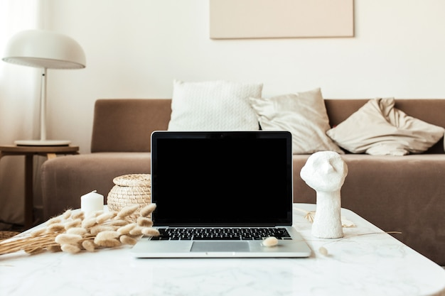 Front view of blank screen laptop on marble table with reeds foliage