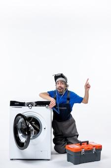 正面図の祝福された修理工が白いスペースに手を上げて洗濯機の近くに座っています