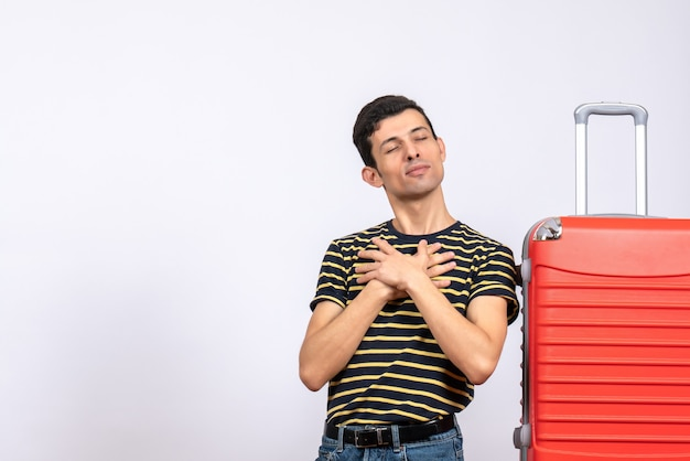 Front view blessed young man with striped t-shirt and suitcase putting hand on his chest