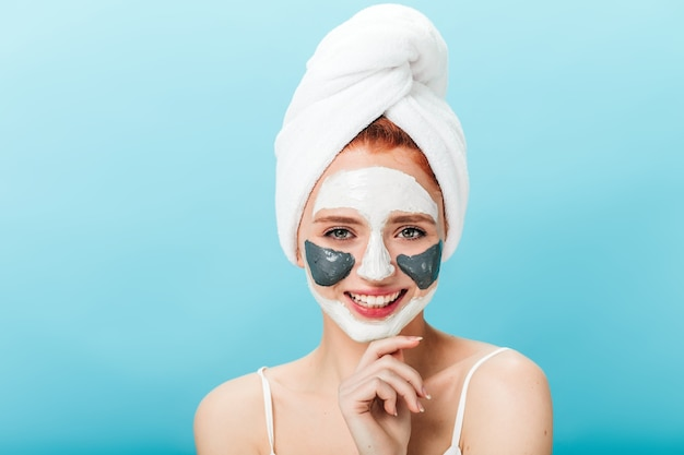 Front view of blissful caucasian woman with face mask. studio shot of pleasant girl with towel on head posing on blue background.