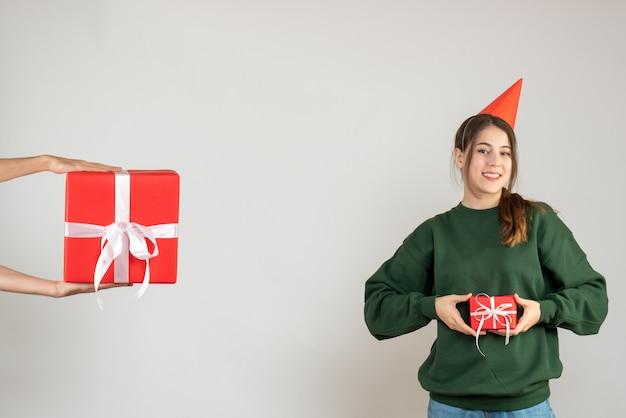 그녀의 크리스마스 선물을 들고 파티 모자와 전면보기 행복 한 소녀