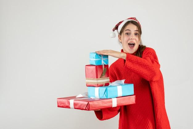 그녀의 크리스마스 선물을 들고 산타 모자와 전면보기 행복 한 소녀