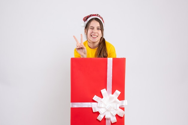 Front view blissful girl with santa hat making victory sign standing behind big xmas gift