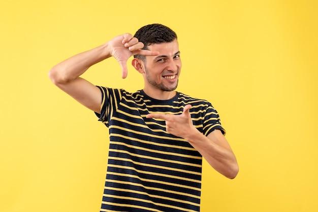 黄色の孤立した背景にカメラのサインを作る黒と白の縞模様のtシャツの正面の至福のハンサムな男