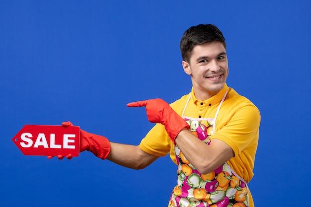 Vista frontale felice governante maschio in maglietta gialla con cartello di vendita su spazio blu