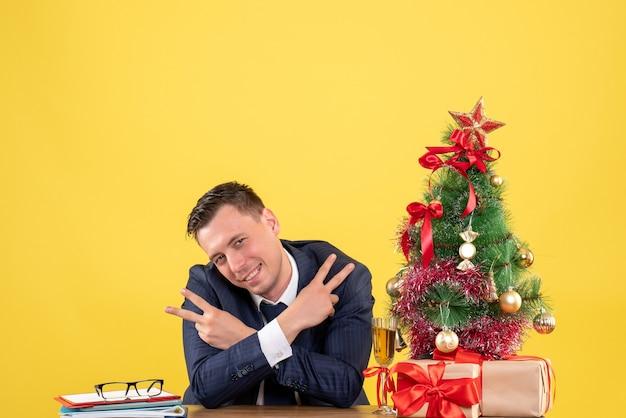 노란색 배경에 크리스마스 트리와 선물 근처 테이블에 앉아 승리 기호를 만드는 전면보기 행복한 사람