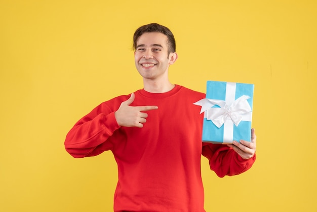 Front view blissful young man with red sweater pointing at hiss gift on yellow