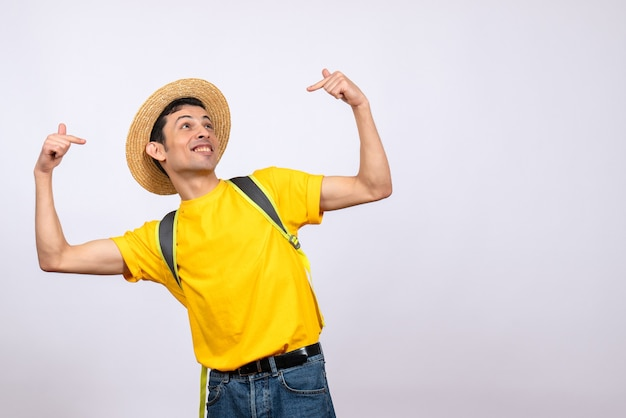 Front view blissful young man withstraw hat and yellow t-shirt pointing at himself