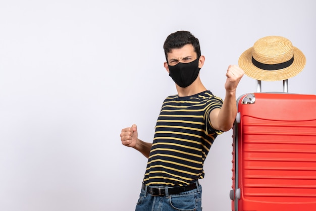 Front view blissful young tourist with black mask standing near red suitcase showing his punches