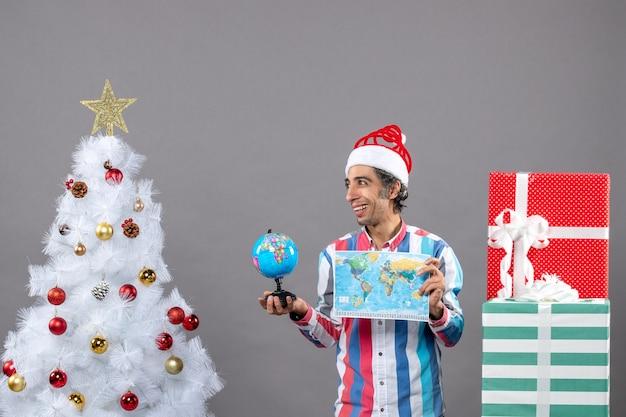 Вид спереди счастливого человека со спиральной весенней шляпой санта-клауса, держащей карту мира и глобус