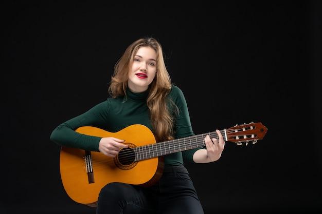 Vista frontale della bella ragazza bionda che suona la chitarra e posa per la macchina fotografica sul nero