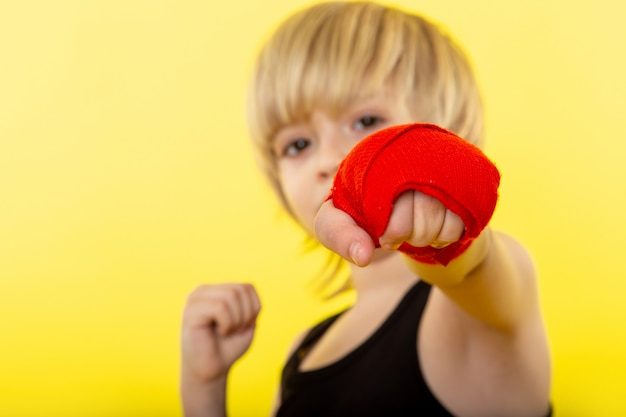 A front view blonde boy adorable boxing in black t-shirt on the yellow wall
