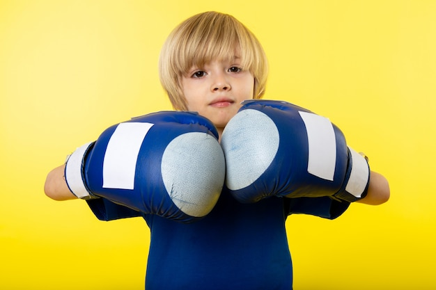 A front view blonde boy in blue gloves and blue t-shirt on the yellow wall