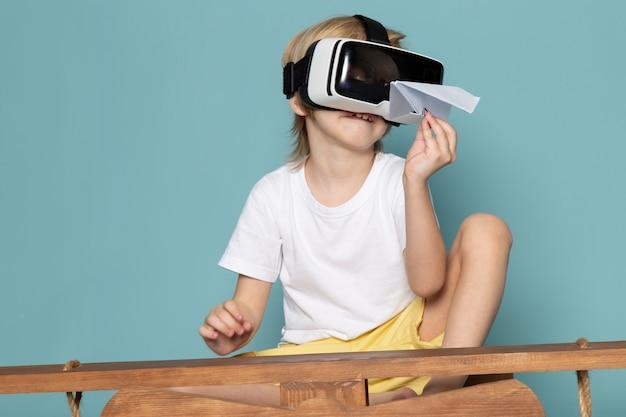 Вид спереди блондинка мальчик играет очки в.р. держит бумажный самолет на синем