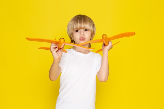 Front view blonde boy playing with orange toy planes in white t-shirt on yellow