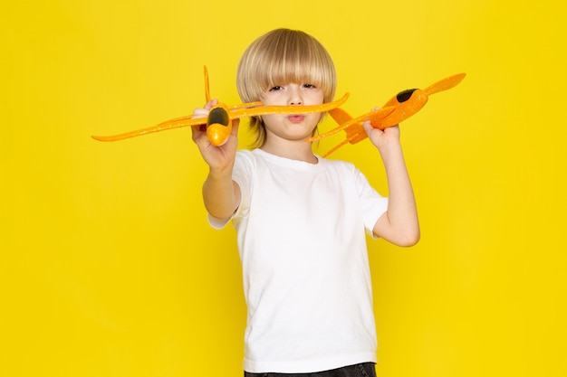 Front view blonde boy playing with toy orange planes in white t-shirt on yellow floor