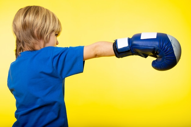 A front view blonde boy posing boxing in blue boxing gloves and blue t-shirt on the yellow wall