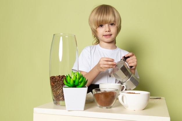 Un ragazzo biondo di vista frontale che sorride in maglietta bianca che prepara la bevanda del caffè sullo scrittorio color pietra
