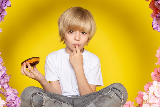 A front view blonde boy in white t-shirt eating choco donuts sitting on the flower made stand on the yellow space