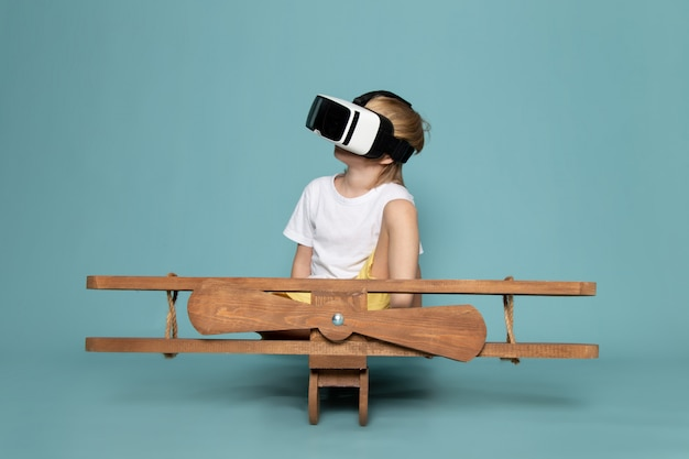 Front view blonde boy in white t-shirt playing vr goggles on the blue floor