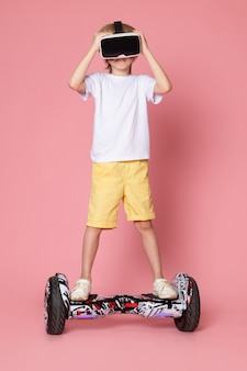 A front view blonde boy in white t-shirt playing vr riding segway on the pink space