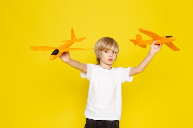 Front view blonde boy in white t-shirt playing with toy orange planes on the yellow floor