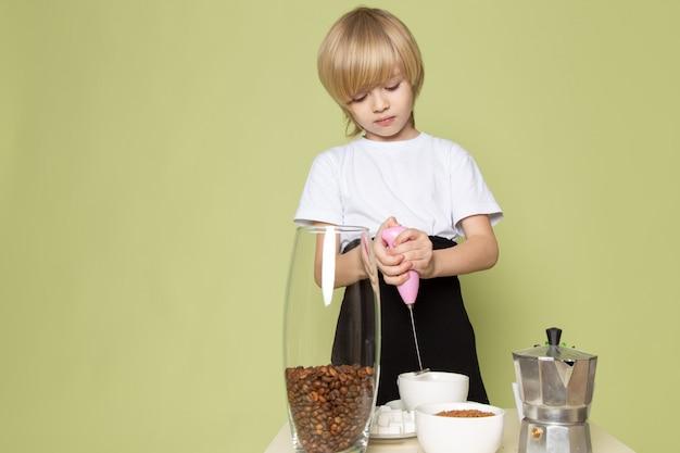 Un ragazzo biondo di vista frontale in maglietta bianca che prepara la bevanda del caffè sullo scrittorio color pietra