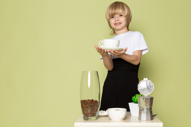 A front view blonde child boy in white t-shirt preparing coffee drink on the stone colored space
