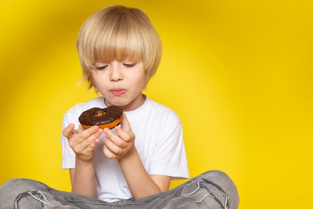 A front view blonde cute boy in white t-shirt eating donuts on the yellow desk