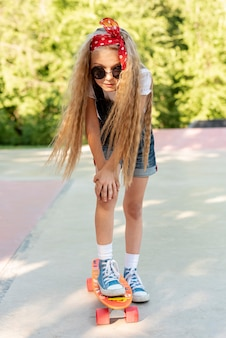 Front view of blonde girl on skateboard