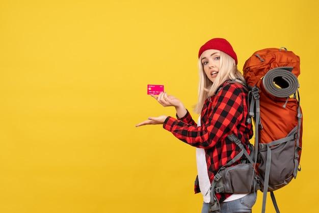 黄色の壁にカードを保持している彼女のバックパックを持つ正面図のブロンドの女の子