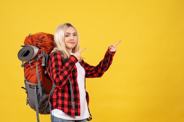 何かを指している彼女のバックパックと正面図のブロンドの女の子