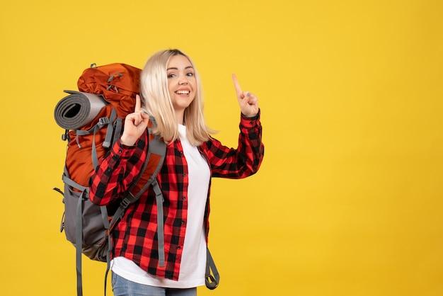 指を上に向けてバックパックを持った正面図のブロンドの女の子